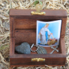 Wooden box containing a heart-shaped stone, a pendant with Virgin Mary, a cross, and a catholic oration.