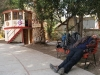 a giant sleeping on a small bench in a small Chilean town